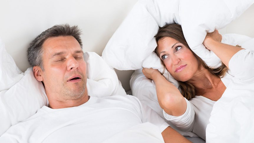 Man snoring while women covers her ears with a pillow - Idaho Falls sleep study