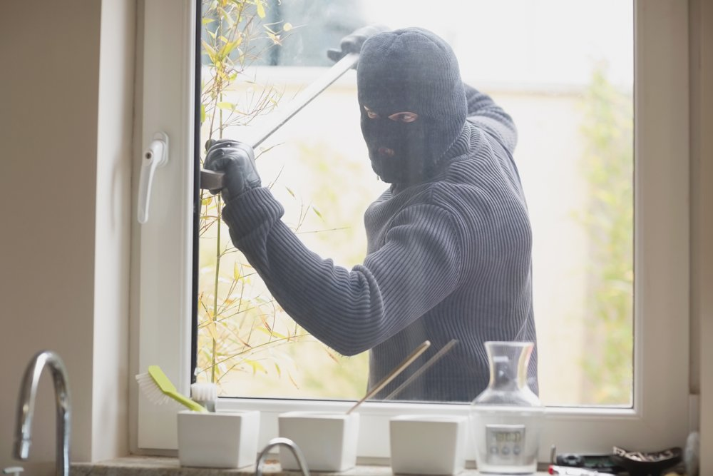 Burglar Breaking Into Home Through Window - Home Burglary Criminal Defense