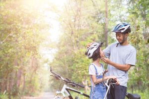 father and child wearing helmets while riding bikes