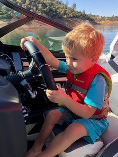 child driving boat