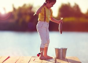 kid putting fish in bucket