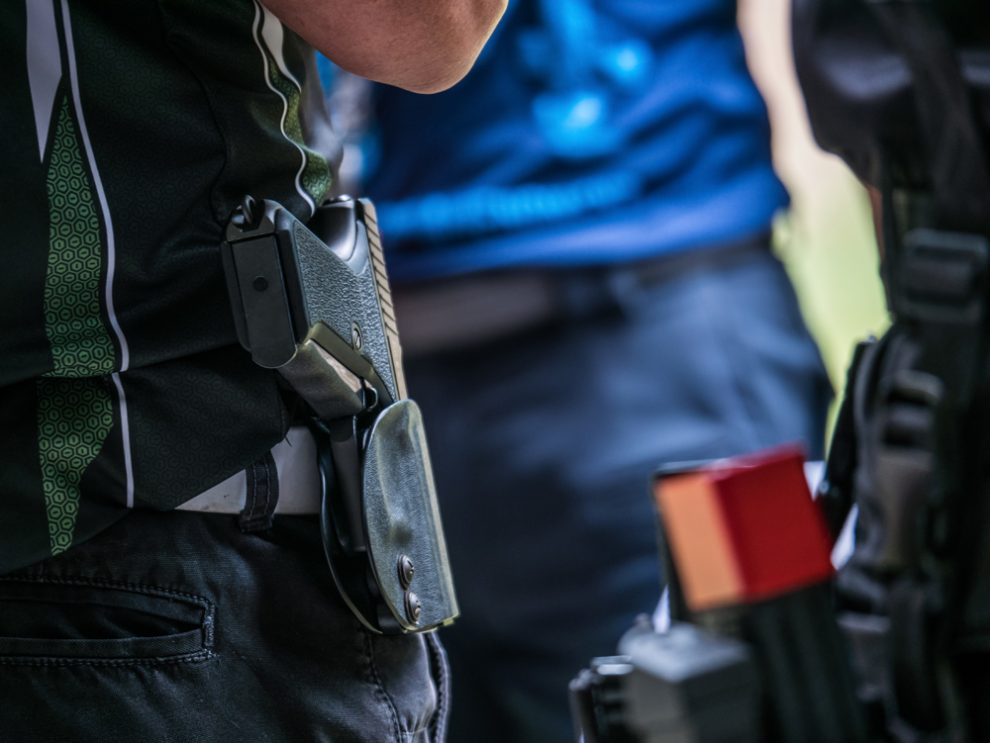 males with handgun in holster standby for shooting competition