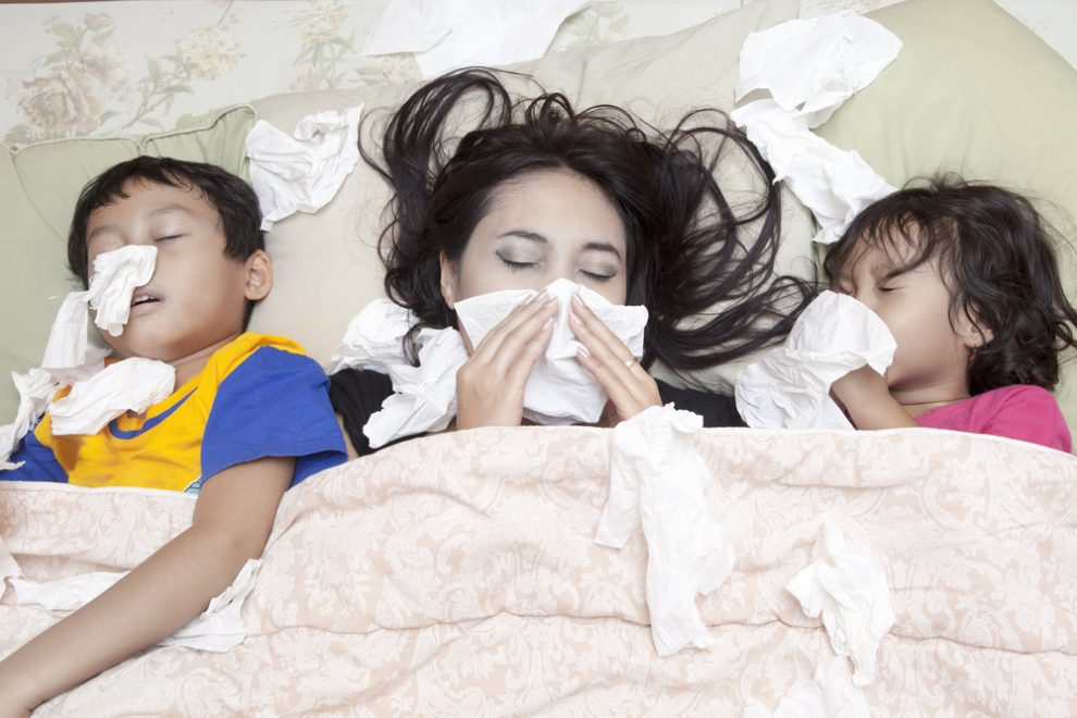 Woman and kids in bed with the flu