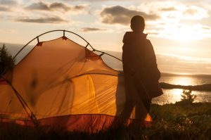 person standing next to tent camping with the sunrise