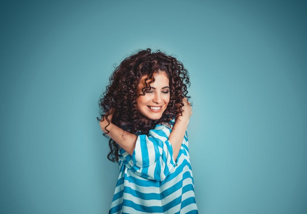 Closeup portrait confident smiling woman holding hugging herself isolated blue wall - COVID -19 Self Care