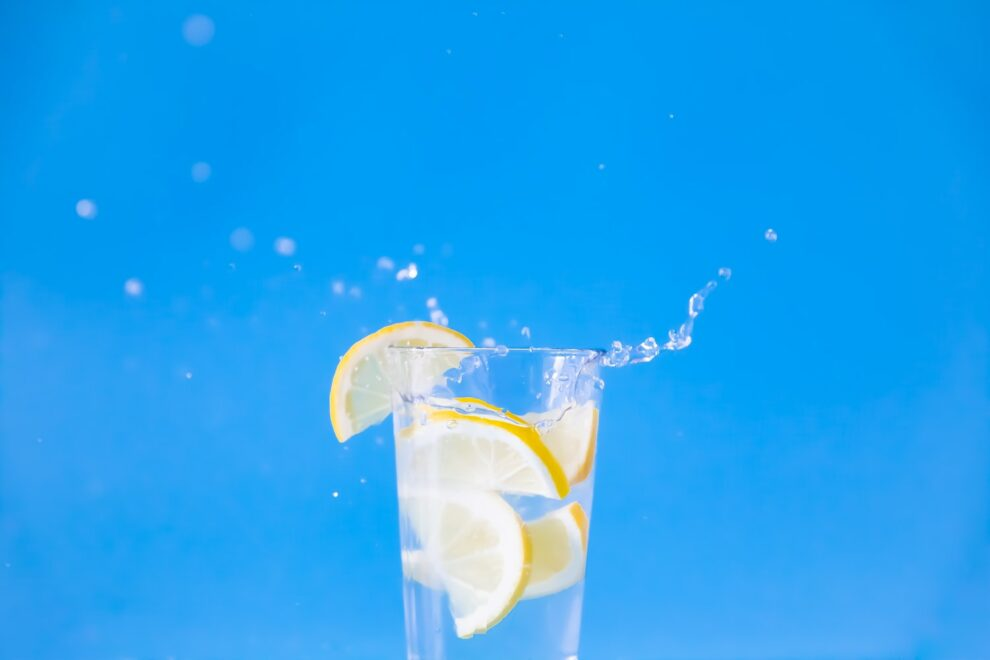 glass of lemon water in front of blue background