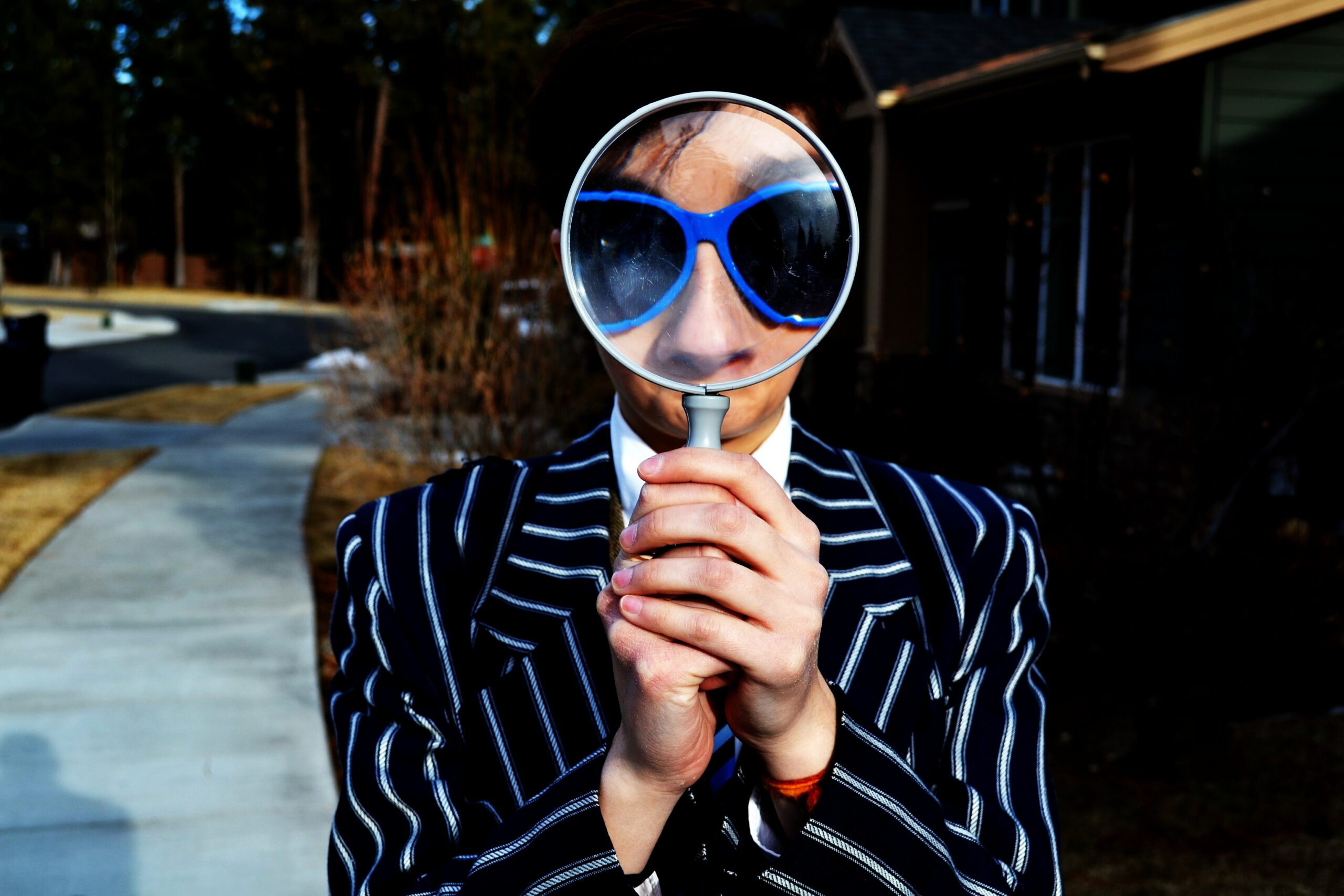 person in a suit with blue sunglasses looking through a magnifying glass